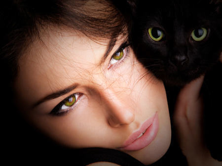cat eye: beautiful young woman portrait with black cat, close up
