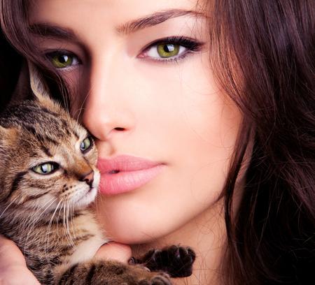 cat eye: beautiful young woman portrait holding kitten, close up