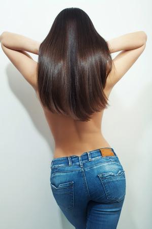 back view of long hair brunette wearing blue jeans, studio white