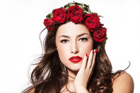 beautiful young woman with red lipstick and a wreath of red roses on her head, studio white Stock Photo