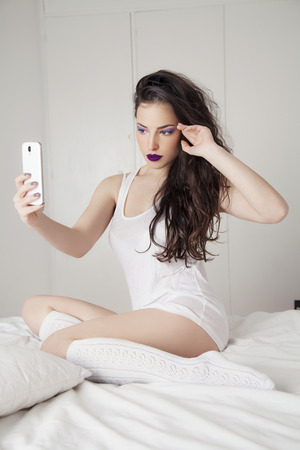 beautiful young woman taking selfie with her smartpnone in badroom