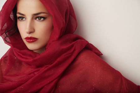 beautiful woman portrait with red lips and red veil over her head, studio shot Stock Photo