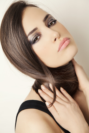 young woman with a healthy and shiny hair, studio beauty portrait