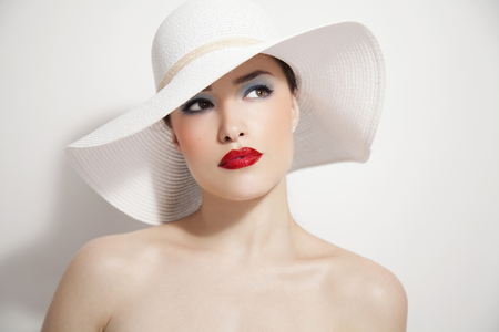 woman beauty portrait with red lips and summer white hat, studio 免版税图像