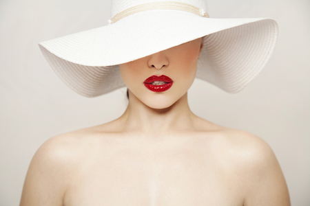 woman beauty portrait with red lips and summer white hat, studio Stock Photo