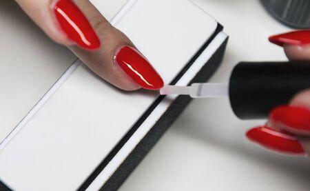 applying red gel nail polish on womens nails Stock Photo