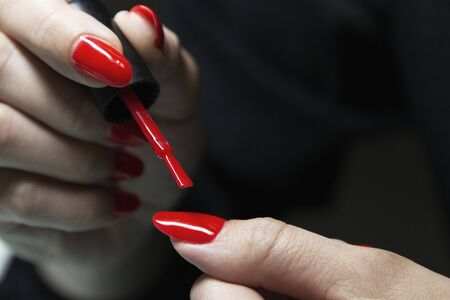 applying red gel nail polish on womens nails Stock Photo
