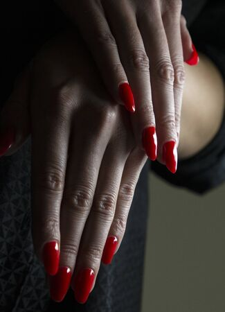 stylishly folded female hands with red manicure on a black background