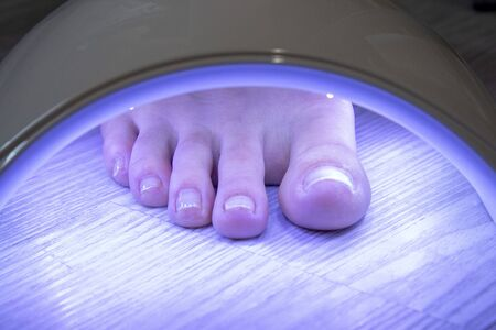 leg to dry under a ultraviolet lamp for manicure