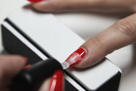 girl puts red gel polish on her nails