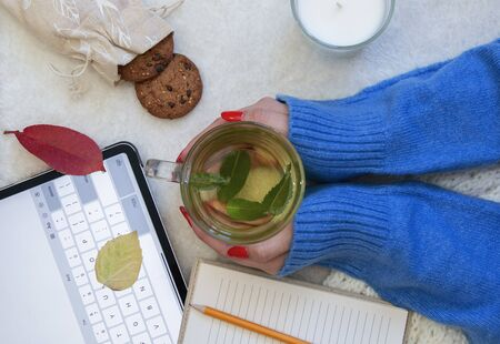 girl in a warm sweater and red manicure drinks mint tea and works Stock fotó