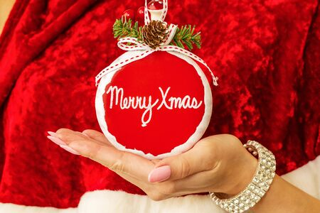 Snow Maidens hand holds stylish new year toy with inscription merry christmas
