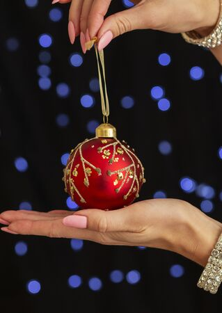 beautiful graceful female hand holds an impressive red Christmas ball.
