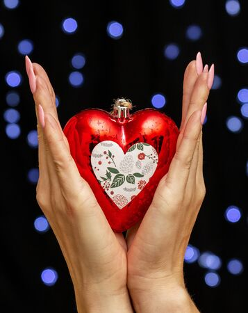 female hands holding heart shaped Christmas toy