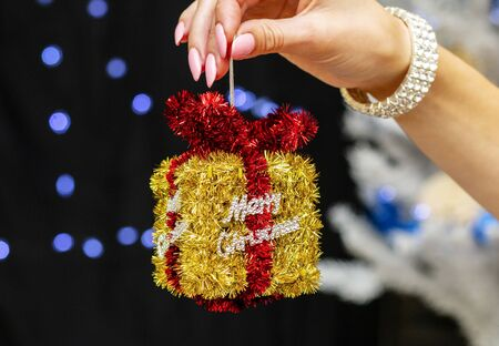 girl holding a beautiful bright new year toy in the shape of a gift and inscription merry christmas Stok Fotoğraf
