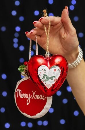 beautiful girl hand holds stylish New Years toys in the shape of a red heart and round with inscription Merry Christmas