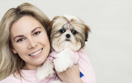beautiful blonde girl with a cute shih tzu puppy in pink clothes on light background