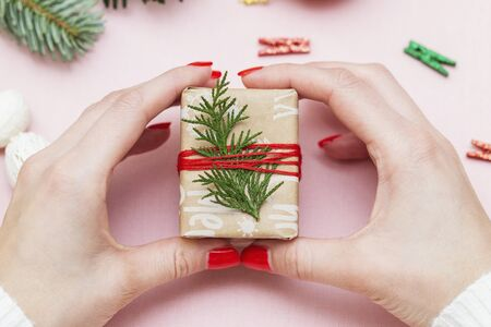 hand made, female hands with beautiful red manicure demonstrate a wrapped gift on pink background