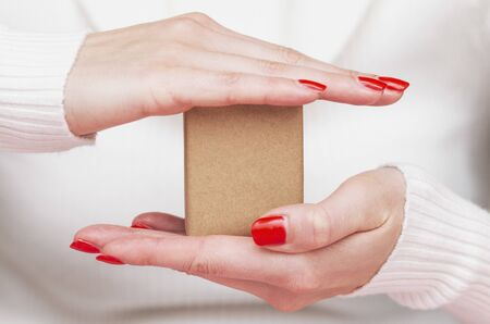 paper box in the palm, delivery insurance, cargo protection, female hands Stock fotó