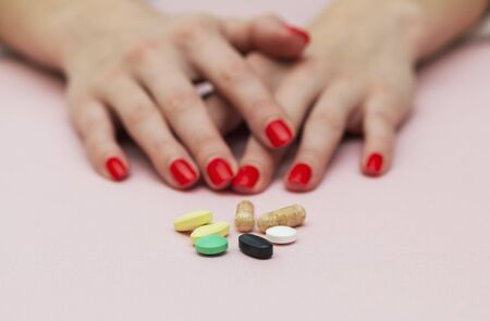 pills on the table, girl folded her arms near the tablets, folded hands, on pink background