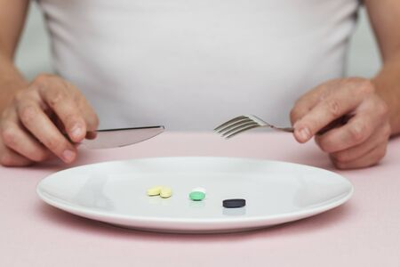 pills on a plate, man eats pills from plate, food supplements Stockfoto