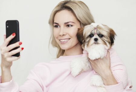 girl takes selfie with shih tzu puppy, posing on the phone, equally dressed, pink clothes