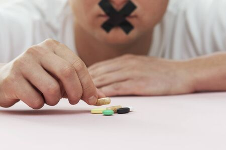 pills on the table, man holds tablet with sticky tape over his mouth Banco de Imagens
