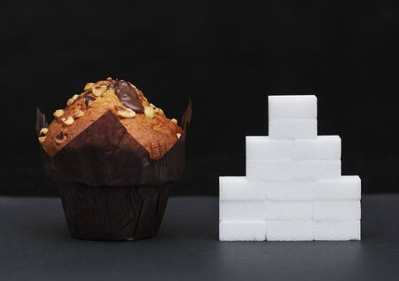 sugar level next to the cupcake, cubes sugar stacked on top of each other, the amount of sugar in dish