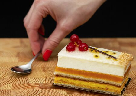 multilayer cake with air cream and red currants on a wooden background, small spoon