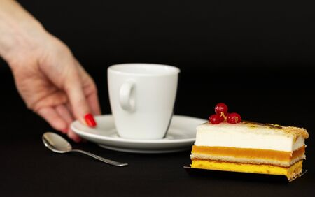 multilayer cake with airy white cream and red currant, mouth watering dessert, white cup with a small spoon