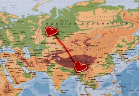 two red hearts on a world map connected by a red thread