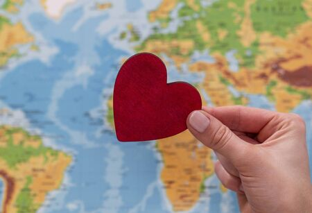man holds red heart on world map background