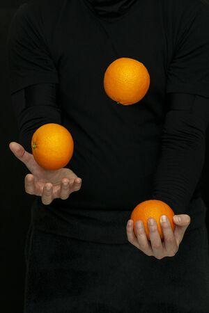 a male hands juggle with fresh oranges on a dark background Banque d'images