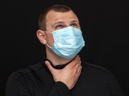 a man puts on a medical mask on his face, instructions on how to wear a mask