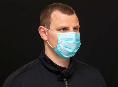 man puts on a medical mask on his face, instructions on how to wear a mask