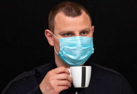 a man with a medical mask drinks coffee on a dark background