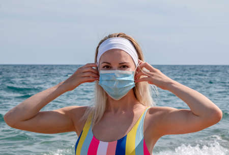 a beautiful girl in a medical mask on the beach