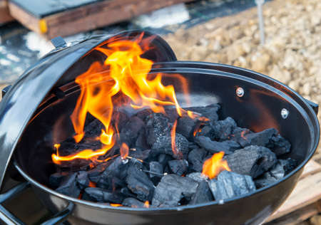 black barbecue with burning coals outside, fire Foto de archivo