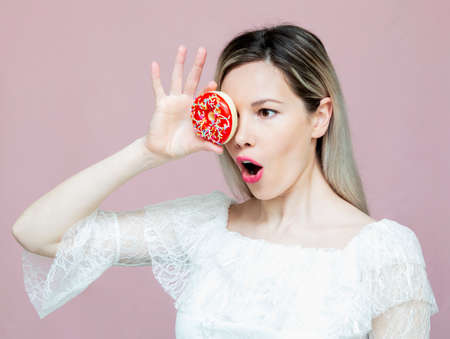 beautiful girl playing with donuts on a pink background. Diet, dieting concept. Junk food, weight loss