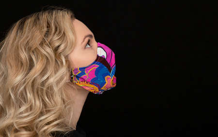 girl in a medical mask with Indian print, hand-made on a dark background