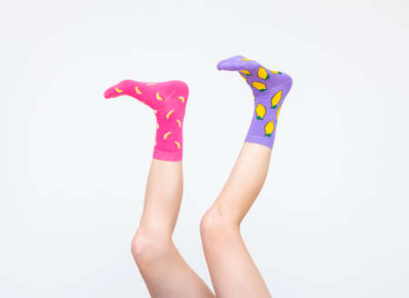 female legs in colorful socks holding banana juggling feet isolated on white background Reklamní fotografie - 163551974