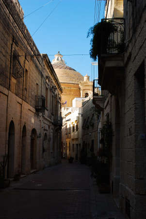 Mosta street with the view on the Mosta Rotunda in the background