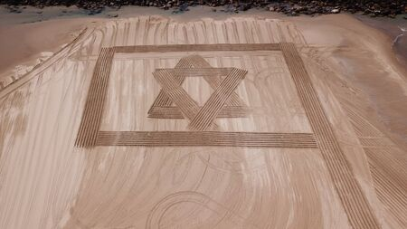 ISRAEL Flag in Sand on a beach. Aerial view.