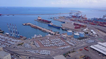 Aerial view on a Port, docking vessels on the platform, containers, and rows of imported new cars.