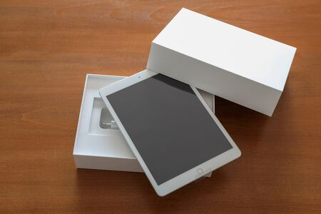 Brand new white tablet with a box on a wooden background.