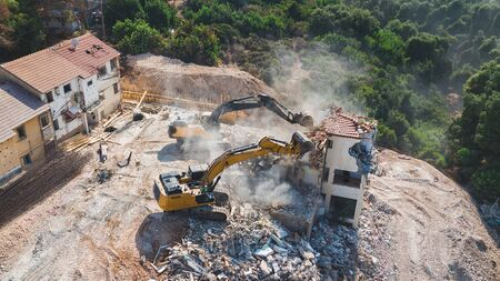 Urban Renewal. Urban Regeneration. Demolition of a building for new construction. Dismantling of a house. Excavator demolishing barracks for new construction project. 写真素材