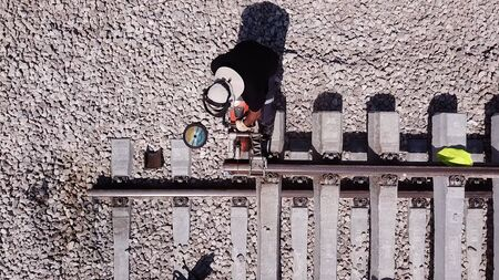 Railroad worker repairing a broken track. Working metal. Worker cutting metal rail tracks. 写真素材