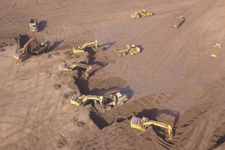 Several Earth moving equipment at new development site. Earth moving machines. Drone view on a New construction site.