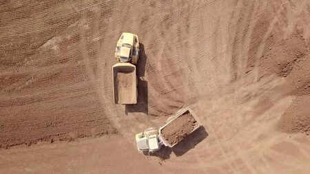 Heavy duty dump truck loaded with soil in a new construction site. Aerial view.