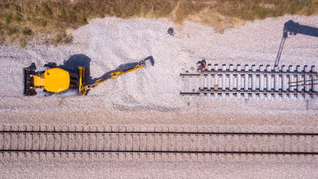 Railroad workers repairing a broken track. Repairing railway. Rail tracks maintenance process.
